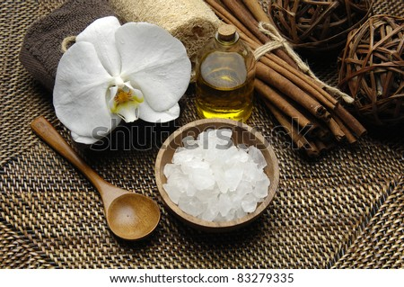 bowl of salt and orchid with massage oil on burlap texture