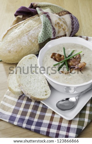 bowl of seafood soup set on a rustic table with a loaf of bread, very inviting