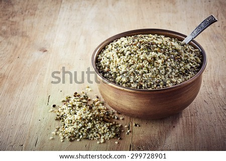 Bowl of shelled hemp seeds on wooden background