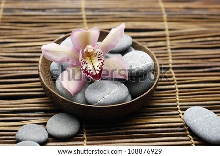 Bowl of spa stone with orchid on mat