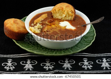 Bowl of spicy Tex-Mex Chili and jalapeno cornbread with melted cheese and dollop of sour cream against black Aztec design place mat.