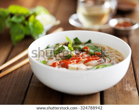 Bowl of vietnamese Pho Tai beef soup with spicy sriracha