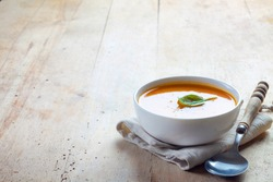 bowl of squash soup on a wooden table