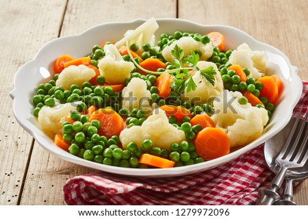 Bowl of steamed fresh frozen mixed vegetables with peas, florets of cauliflower and diced carrots