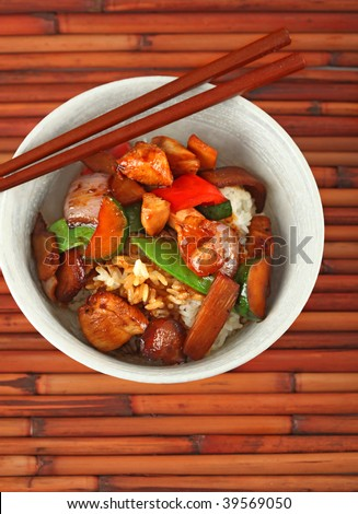 Bowl of Stewed Chicken and Vegetables over White Rice on Bamboo Placemat