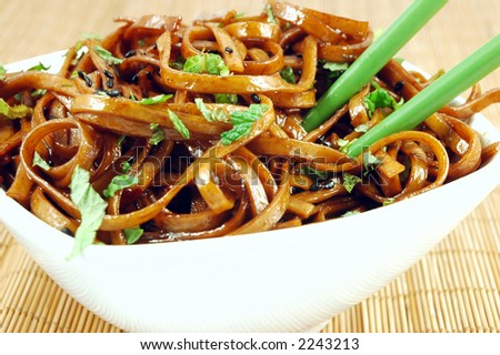 Bowl of stir fried udon noodles garnished with black sesame seeds and fresh mint with green chopsticks