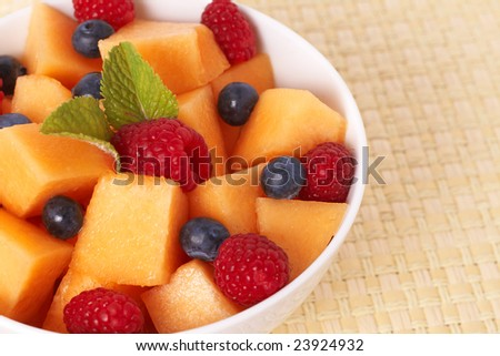 stock photo : Bowl of summer fruit salad with raspberries, melon,