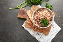 Bowl of tasty buckwheat porridge on table, top view