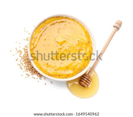 Bowl of tasty honey mustard sauce on white background Foto stock ©