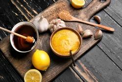 Bowl of tasty honey mustard sauce with ingredients on dark wooden background