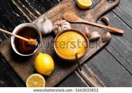 Bowl of tasty honey mustard sauce with ingredients on dark wooden background Foto stock ©