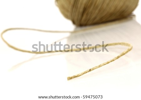 Bowl of thread with one end loosened on a white background