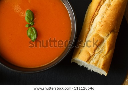 Bowl of tomato soup and basil garnish with bread baguette