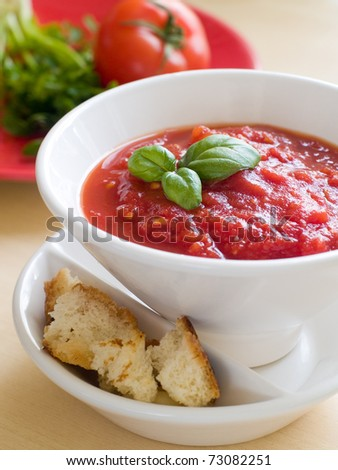 Bowl of tomato soup with bread crouton and basil