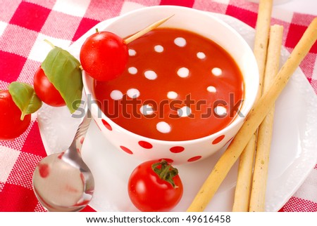 bowl of tomato soup with cream drops and with grissini