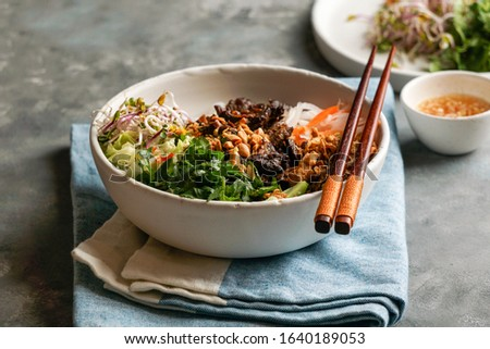 bowl of traditional Vietnamese noodle salad - Bun Bo Nam Bo, with beef, rice noodles, fresh herbs, pickled vegetables and fish sauce Stok fotoğraf ©