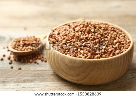 Bowl of uncooked buckwheat on wooden table