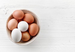 bowl of various fresh eggs on white wooden table, top view