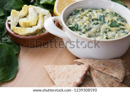 Bowl of vegan spinach artichoke dip with pita and ingredients. #1239308590