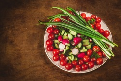 bowl of vegetables on wooden background in top view