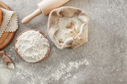 Bowl of wheat flour and sackcloth bag with scoop on light background