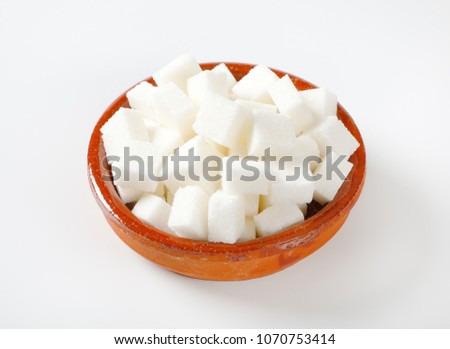 bowl of white sugar cubes on white background #1070753414