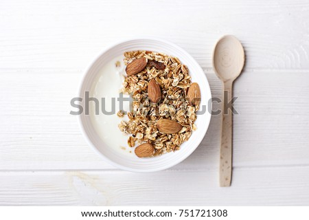 Bowl of whole grain muesli with yogurt on white background, top view