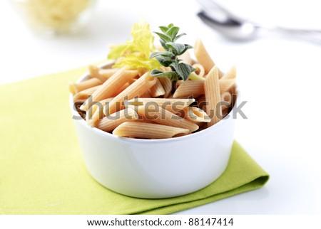 Bowl of whole wheat pasta tubes - closeup