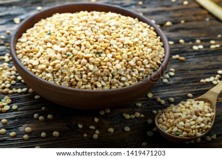 Bowl of yellow dry split peas on wooden background . Top view #1419471203