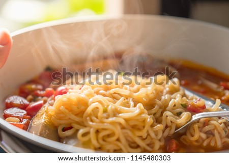 bowl ramen soup. Instant noodles Tom Yum Koong with egg and celery on wood table,hot bowl