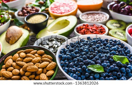 Bowl with almonds, bilberry, fresh fruit and other healthy food. Organic breakfast with vegetarian nutrition. Super foods collection on table.