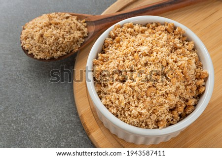 Bowl with Brazilian farofa with soy protein. Detail of wooden spoon and bamboo holder.