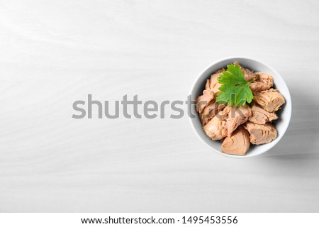 Bowl with canned tuna on light table, top view. Space for text