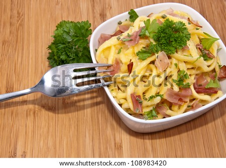Bowl with Cheese Spaetzle and cutlery on wooden background