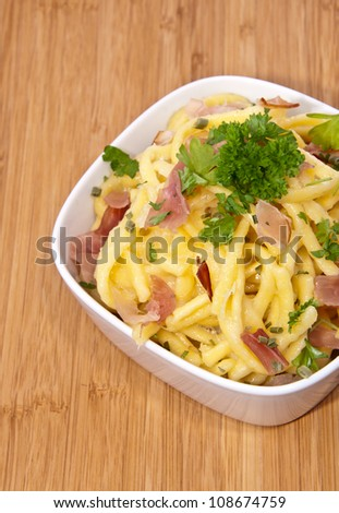 Bowl with Cheese Spaetzle on wooden background (decorated with Parsley)