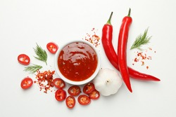 Bowl with chilli sauce, pepper and garlic on white background