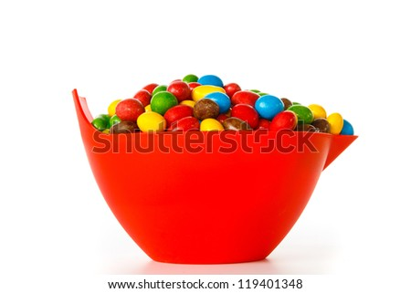 Bowl with colorful chocolate sweets against white background