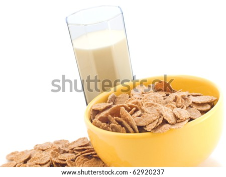 Bowl with corn flakes and milk in the glass on a white background - stock photo