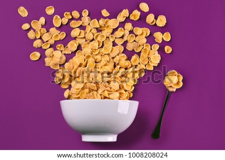 Bowl with corn flakes and spoon on purple background, top view