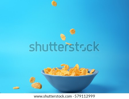 Bowl with corn flakes on blue background #579112999
