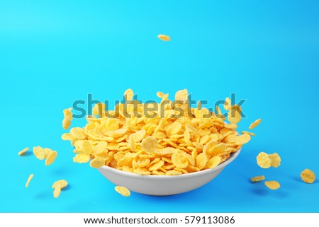 Bowl with corn flakes on blue background #579113086