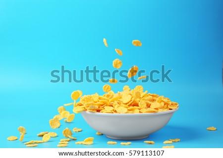 Bowl with corn flakes on blue background #579113107