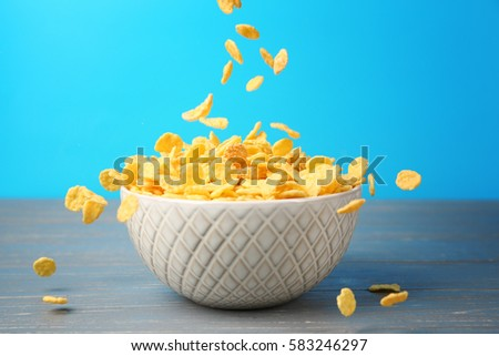Bowl with corn flakes on blue background #583246297