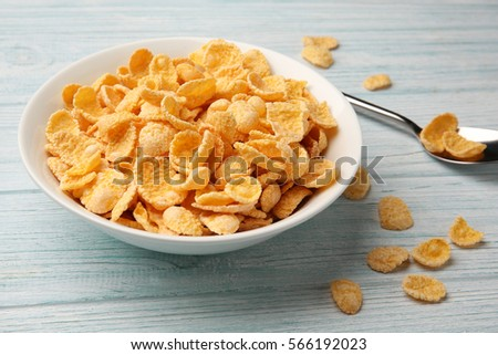 Bowl with cornflakes on white wooden background #566192023