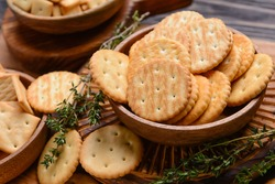 Bowl with crackers on wooden background