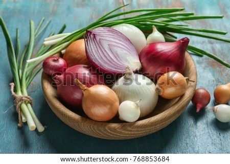 Bowl with different onions on color wooden table