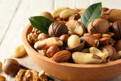 Bowl with different tasty nuts on white wooden background