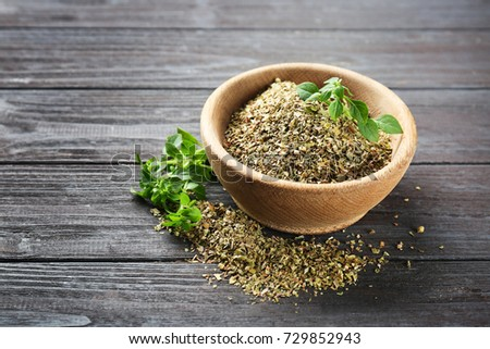 Bowl with dried oregano on wooden table #729852943