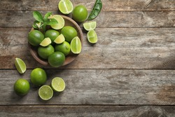 Bowl with fresh ripe limes on wooden background, top view