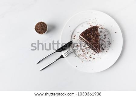 Bowl with grated chocolate and cake on plate